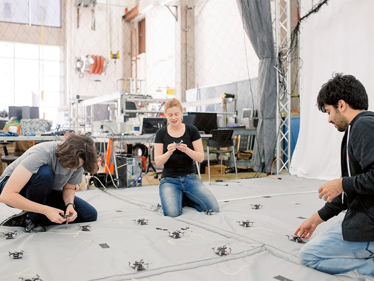 FILE -- From left: Dimitris Konstantinidis, Ellen Cappo and Arjav Desai place batteries into drones at the Robust Adaptive Systems Lab, part of Carnegie Mellon's Robotics Institute, in Pittsburgh, May 26, 2017. After losing top professors, college students are less likely to create artificial intelligence start-ups and get less venture funding, the research says. (Kristian Thacker/The New York Times)