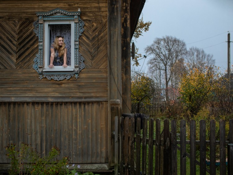 **EMBARGO: No electronic distribution, Web posting or street sales before Saturday 3:01 a.m. ET Oct. 24, 2020. No exceptions for any reasons. EMBARGO set by source.** Marina Udgodskaya, recently elected as the mayor of Povalikhino, Russia, looks out the window of her home in the tiny village some 300 miles northeast of Moscow, Oct. 15, 2020. Udgodskaya was the cleaning lady at city hall, and had been asked by the former mayor to run in order to help create the illusion of democratic choice; her win precipitated a national media frenzy. (Emile Ducke/The New York Times)