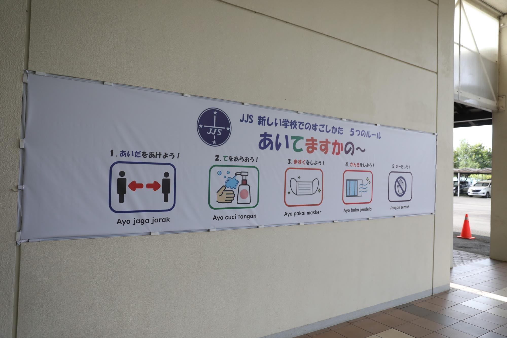 ジャカルタ日本人学校の校舎入り口に掲げられた横断幕「新しい学校でのすごしかた 五つのルール」。朝日新聞ジャカルタ支局の野上英文記者が2021年3月、南タンゲラン市で撮影。