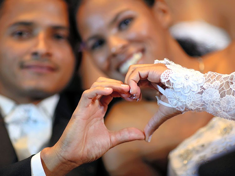 A couple makes a sign in the shape of a heart during a mass wedding ceremony at the Museum of the Republic in Brasilia March 23, 2013. Seventy-eight couples participated in the mass wedding as part of the fifth edition of Alma Gemea project, which is sponsored by the Department of Justice, Human Rights and Citizenship of the Federal District. REUTERS/Ueslei Marcelino (BRAZIL - Tags: SOCIETY)
