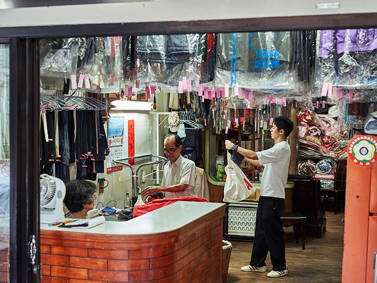 Reef Chang, right, who dreamed up the Instagram account idea for the laundry business of his grandparents Hsu Sho-er, left, and Chang Wan-ji, at the business in Taichung, Taiwan, July 23, 2020. The octogenarian owners of Wansho Laundry in central Taiwan have become Instagram stars for posing in garments left behind. (An Rong Xu/The New York Times)