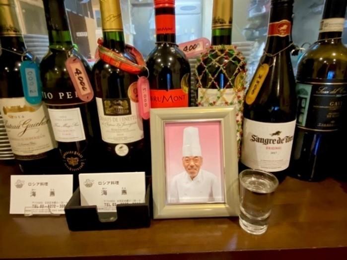 店のキッチンの横には、毛塚さんの写真が飾られている。好きだったウォッカが供えられている=瑠美さん提供