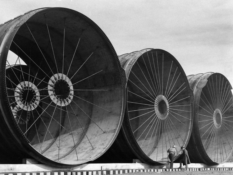 View of relief workers standing next to several of the giant pipe sections used to divert the Missouri River during the construction of the Fort Peck Dam in Montana, ca. 1936.ツ