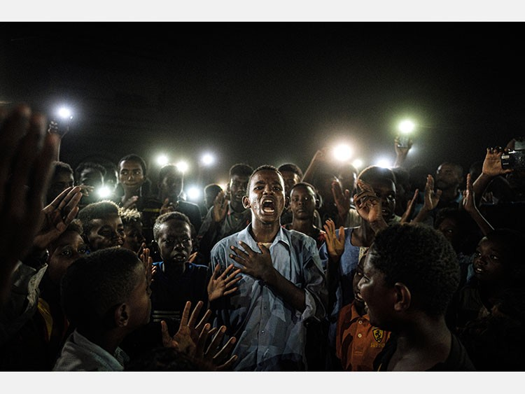 People chant slogans as a young man recites a poem, illuminated by mobile phones, before the opposition's direct dialog with people in Khartoum on June 19, 2019. - People chanted slogans including