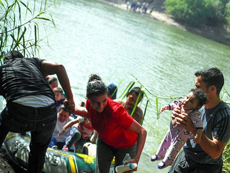 Family units from Central America await their turn on the Mexico side of Rio Grande river as Eliani Valentin, a five-month-old girl from Honduras, is held by a man after a group used a raft to illegally cross into the U.S. from Mexico in Granjeno, Texas, October 5, 2018. Reuters photographer Adrees Latif: