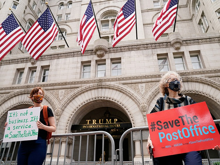 Protestors wearing face masks rally in support of the United States Postal Service (USPS) outside the Trump International Hotel in Washington, U.S. August 22, 2020. REUTERS/Erin Scott