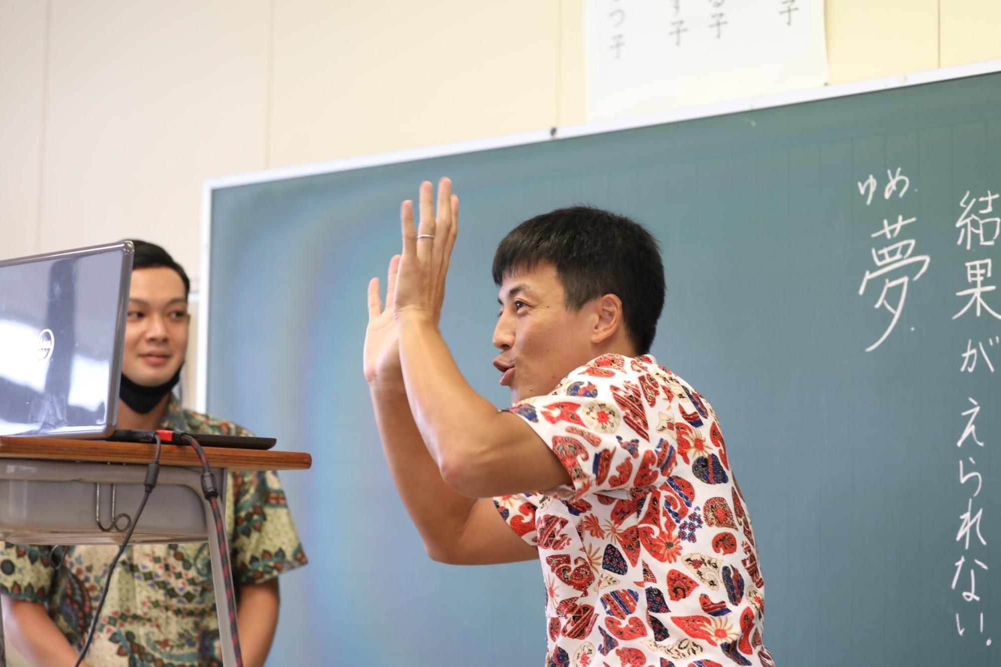 両手を上げながら笑顔でオンライン授業のカメラ前に現れた北岡良仁教諭。朝日新聞ジャカルタ支局の野上英文記者が2021年3月、南タンゲラン市で撮影。