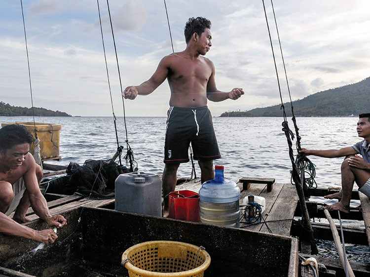 **EMBARGO: No electronic distribution, Web posting or street sales before Tuesday at 3 a.m. ET March 31, 2020. No exceptions for any reasons. EMBARGO set by source.** Basri, center, and other Indonesian crew on a fishing boat in waters near Indonesia's Natuna Islands, in the South China Sea, Jan. 30, 2020. Backed by armed Chinese Coast Guard ships, Chinese fishing fleets have been raiding the rich waters of the South China Sea that are internationally recognized as exclusively Indonesia's to fish. (Adam Dean/The New York Times)