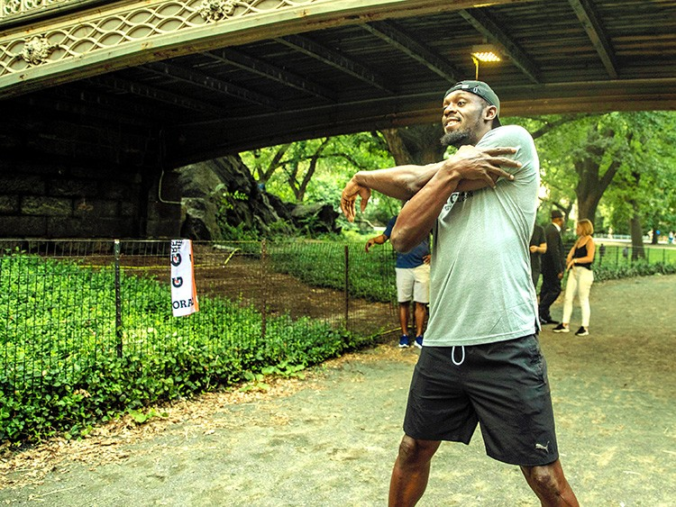 Usain Bolt stretches with members of New York Road Runners in Central Park, New York on July 25, 2019. The world's fastest man has retired from competition, but Bolt is still on the move — and playing pickup soccer. (Brittainy Newman/The New York Times)