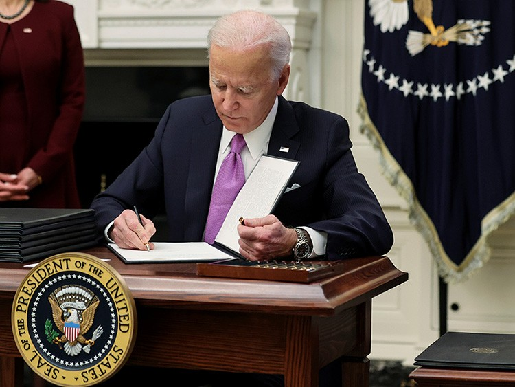 U.S. President Joe Biden signs an executive order as part of his administration's plans to fight the coronavirus disease (COVID-19) pandemic during a COVID-19 response event at the White House in Washington, U.S., January 21, 2021. REUTERS/Jonathan Ernst