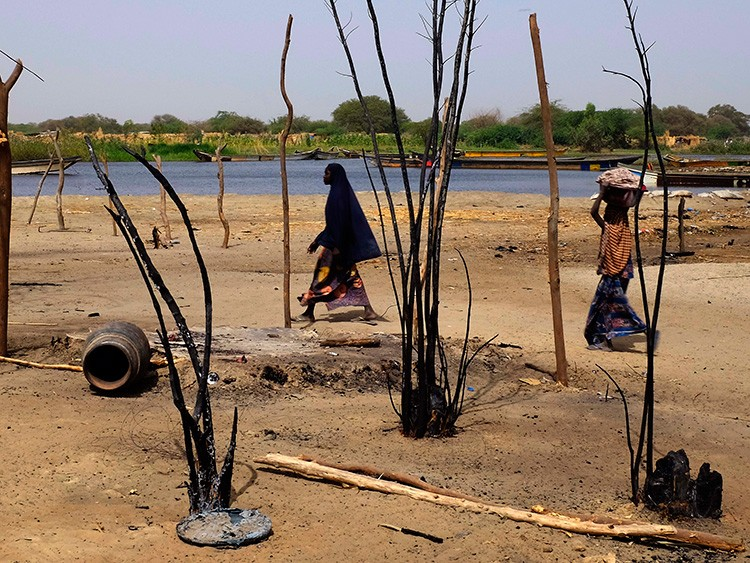 Chadian women walk past destroyed homes, in the Lake Chad shore village of  N'Gouboua, Thursday, March 5, 2015. Boko Haram militants arrived in N窶冏ouboua before dawn on Feb. 13, marking the first attack of its kind on Chad. By the time the scorched-earth attack ended, they had burned scores of mud-brick houses by torching them with gasoline and had killed at least eight civilians and two security officers. Some 3,400 Nigerian refugees had been living in te village at the time of the attack, and all have since been relocated further inland. (AP Photo/Jerome Delay)