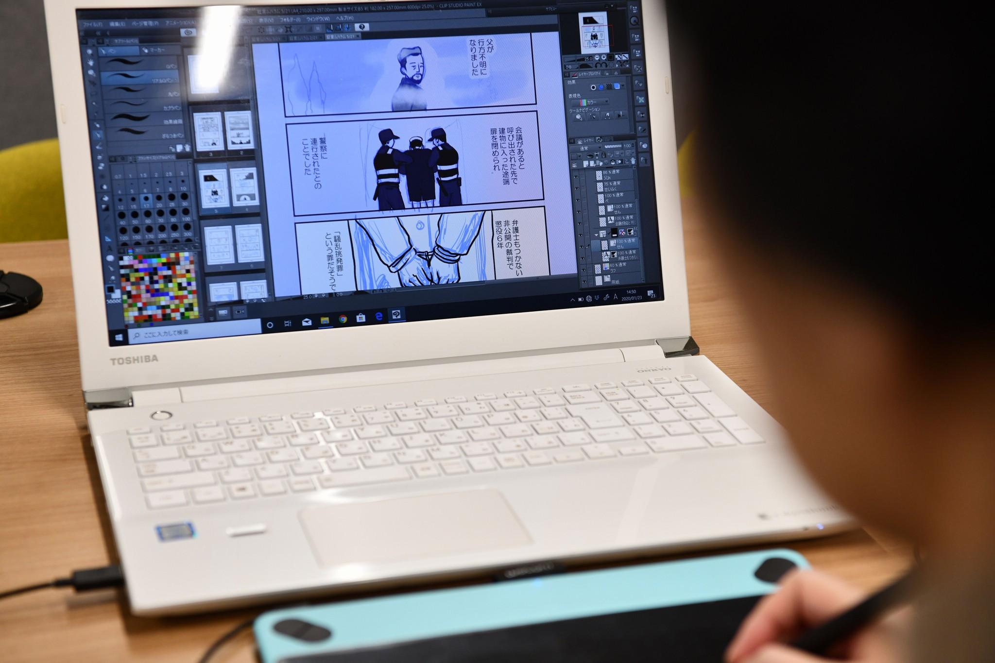 パソコンで漫画を制作する清水ともみさんの写真。奥に漫画が映し出されたノートパソコンがあり、手前に後ろ姿の清水さんが写っている