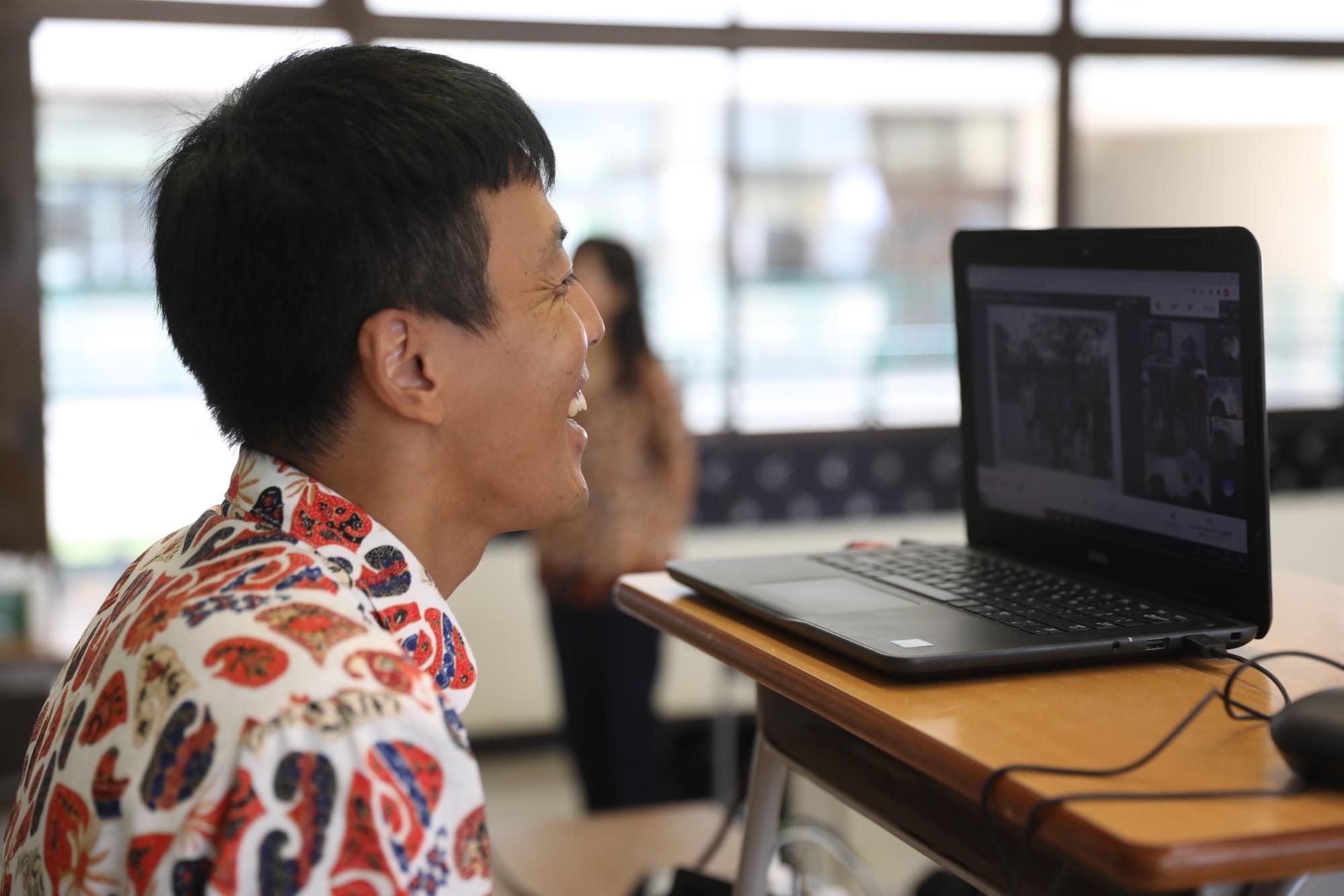 オンライン授業でパソコンに向かって話す北岡良仁教諭=2021年3月、南タンゲラン市、野上英文
