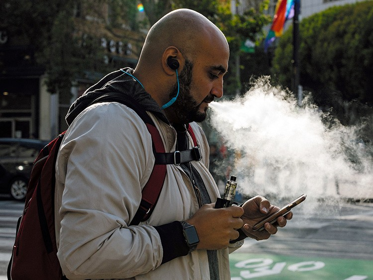 FILE -- A man uses a vaporizer in San Francisco, Calif., June 20, 2019. A person in Illinois has died from a mysterious lung illness apparently associated with an unknown vaping product, public health officials said in August. (Jason Henry/The New York Times)