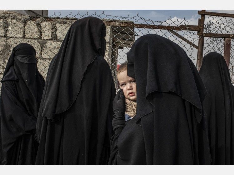 Al-Hol camp section for ISIS foreign fighters women. In the photo, a Russian child in his mother's arms, who together with other foreign women await authorization of going to buy food at the grocery store of the camp. A Russian woman is holding her baby, queueing at the makeshift hospital of the Annex, the side of al-Hol camp where 10.000 people of 48 different foreign nationalities live in the tents.
