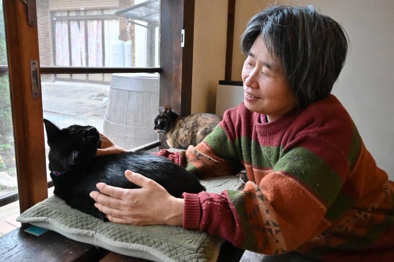 保護猫カフェ経営者の榊原裕美さんと黒猫