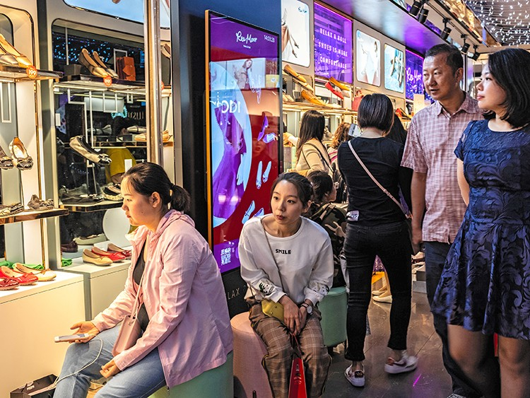 Shoppers look at shoes in a Beijing mall, May 18, 2019. Chinese consumers, who have become more cautious over the past year, are now staging a broad retreat. They are buying fewer cars, smartphones and appliances, going to the movies less and taking fewer trips abroad. (Lam Yik Fei/The New York Times)
