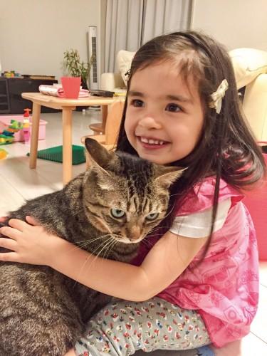 キジトラ猫を抱く女の子