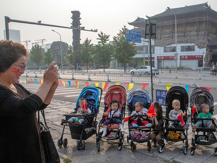 FILE -- Babies hold Chinese flags in their strollers in Beijing, Oct. 1, 2019, as China celebrates 70 years of Communist Party rule. The number of babies born in China last year fell to a nearly six-decade low, exacerbating a looming demographic crisis that is set to reshape the world's most populous nation and threaten its economic vitality. (Gilles Sabrié/The New York Times)